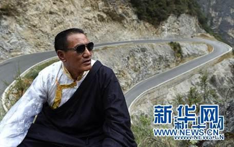 斯那定珠在香格里拉大峡谷内仰望远方(他的一只眼睛近乎失明,经常戴着墨镜),身后是其倾尽所有修建的其中一段公路(2016年5月14日摄)。新华社记者蔺以光 摄