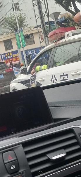 网民举报的交警驾警车抽烟照。(供图)