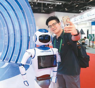 6月20日,在2018世界交通运输大会科技博览会上,观众与服务型机器人自拍。陈晓根摄(人民视觉)