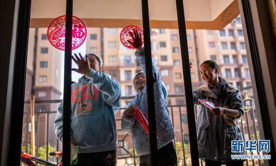 石元顺的女儿们在贴窗花(2月11日摄)。