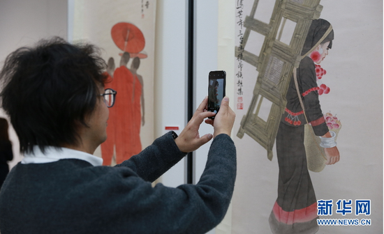 图为一名观众用手机拍摄展出的画作。(新华网 罗春明摄)