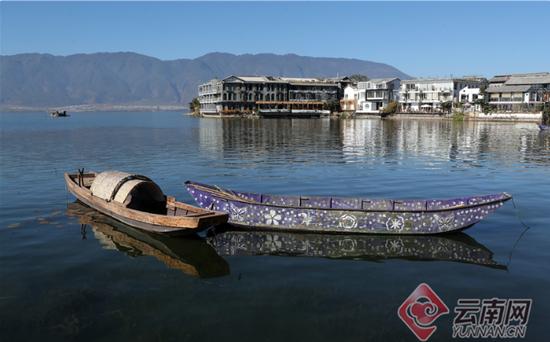 """具有乡土特色的木舟和湖面保洁的""""花船""""。记者 杨峥 摄"""