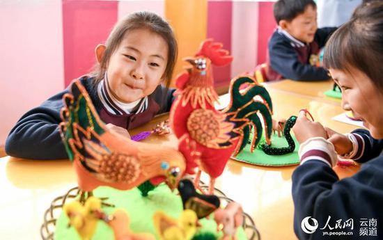 """5月29日,在""""六一""""国际儿童节到来之际,云南剑川白族布扎类非遗传人走进幼儿园,为小朋友们开展非物质文化遗产传承。(苏金泉、赵雁摄)"""