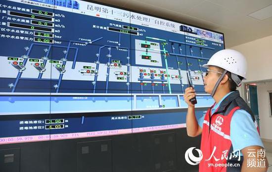 9月17日,一名工作人员正在生产调度中心通过对讲机与地下工作人员进行设备工艺调试交流。(人民网 虎遵会 摄)