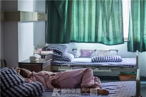 """一位患者躺在病房里的床上休息,红色的病号服,表明她属于""""一级护理""""对象。"""
