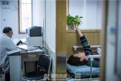 一位患者在等待治疗时,伸手触摸桌上的绿植。