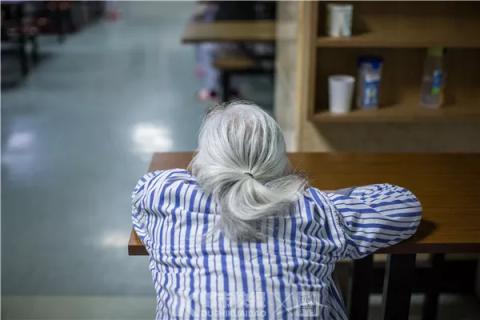 一位患者趴在桌上,不发一言。