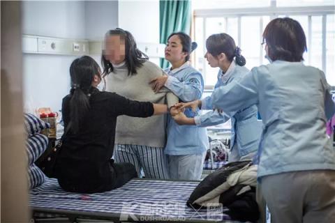 病房里,一位发病的患者对着母亲大吼大叫,还差点动手,护士们赶紧进来劝阻。