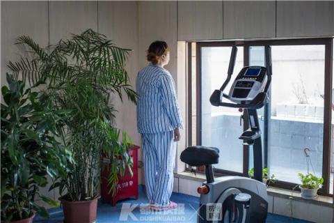 一位患者打开康复中心的一扇窗,一边吹风,一边看着窗外。