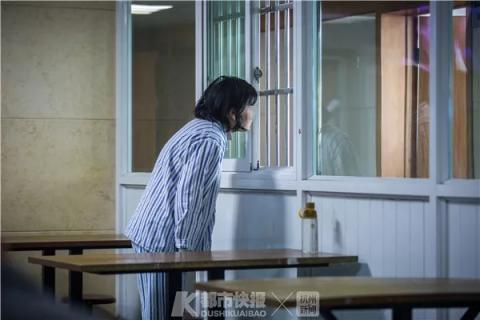 一位患者透过病区的窗户,朝对面的医生办公室张望。