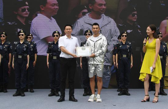 """图为:赵文卓接过""""杭州西湖女子巡逻队成长导师""""聘书。王刚 摄"""