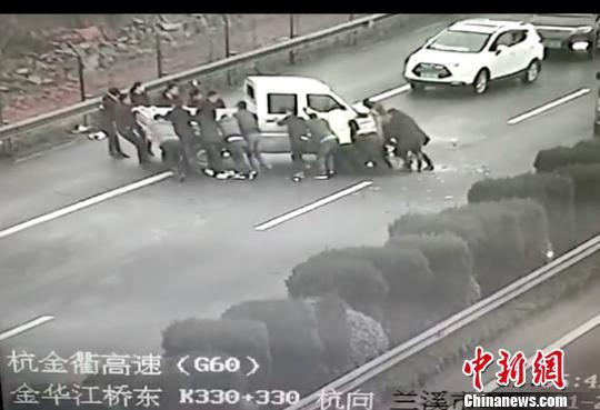 众人齐力抬车。金华高速交警提供