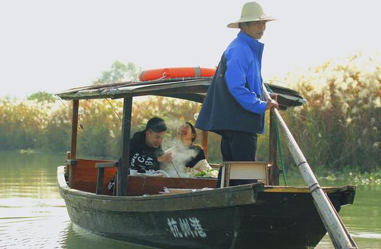 图为:游客乘船荡漾在芦花旁。杨作英 摄