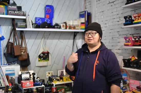 图为:相机店工作人员在作相机介绍。 王刚 摄