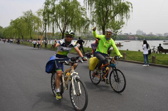 图为:两位骑行爱好者在西湖白堤上骑行。 王刚 摄