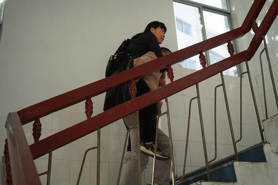 丈夫李海龙背着陈文娟去上课。 本文图片均来自浙江新闻客户端