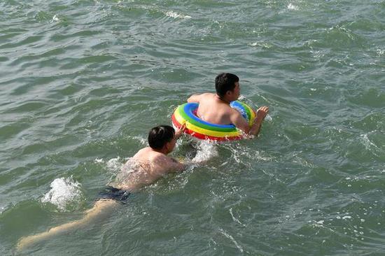 本周金华气温突破38℃,市民纷纷前往市区铁堰等地游泳找清凉。时补法摄