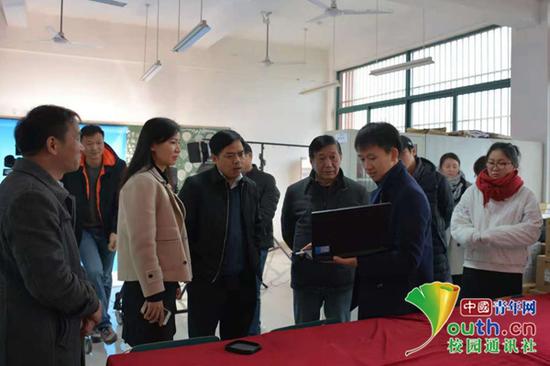 图为安徽大学艺术与传媒学院汪博(前排右一)在为老师介绍校媒作品。本人供图