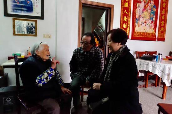 胡汉英和胡汉平在招士湾村和闾儒香儿时的玩伴王水英在一起交谈