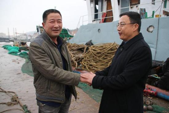 舟山市普陀区委副书记、六横管委会主任徐炜波(右)在码头慰问干飞岳等船员。