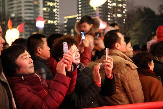 图为:市民用手机拍摄花灯。柱子(通?#23545;保?#25668;