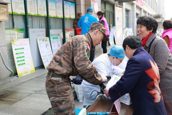 支队官兵接过待修理的电热锅。武警浙江省总队机动支队供图