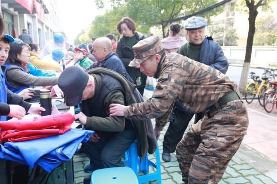 支队官兵们细心地为居民检查身体。武警浙江省总队机动支队供图