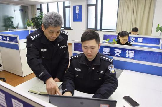 图为:方良明与同事交接工作 刘冰菲 摄