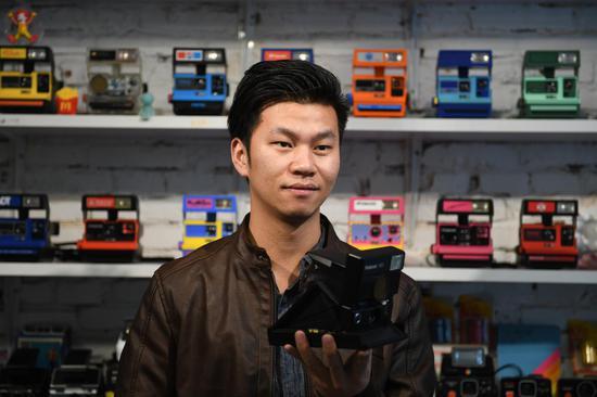 """图为:""""精彩哥""""展示其收藏的相机。 王刚 摄"""