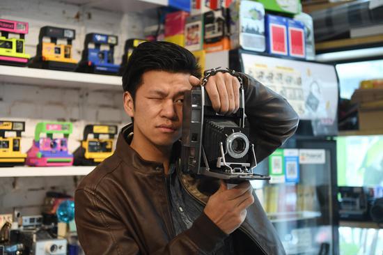 """图为:""""精彩哥""""用相机拍照。 王刚 摄"""