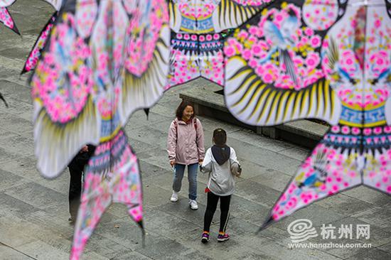 游客们漫步在风筝下享受惬意的时光。