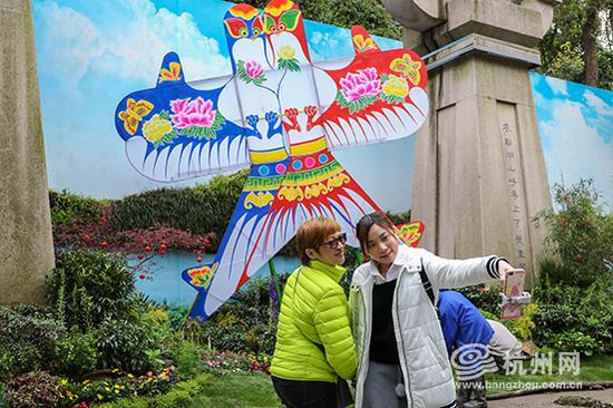 景区门口的巨型风筝吸引着游客们纷纷驻足拍照留念