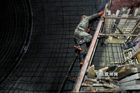 一位工人正爬上衬砌台车,准备工作。