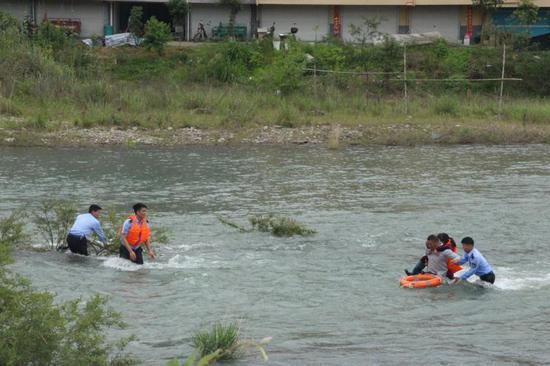 洗衣被困河中央 浙江丽水警民火速救援助其渡河。叶金芬摄