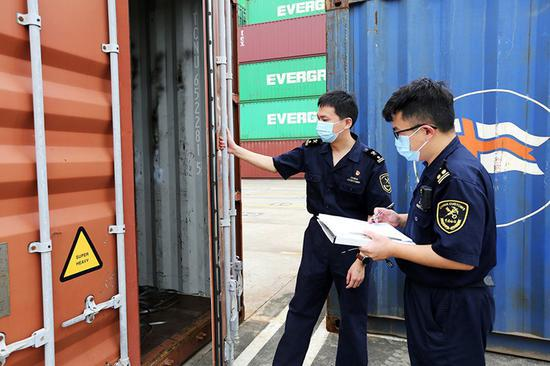 海关关员对开箱查验待退运固体废物。姚峰摄