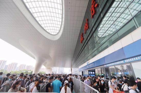 杭州东站东进站口,旅客在有序排队进站。周围摄