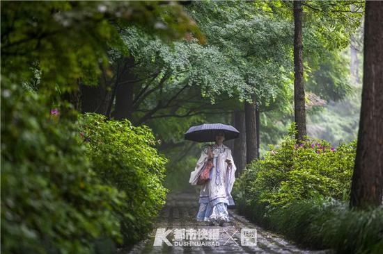 雨中灵隐路,一位汉服女孩打伞经过。首席记者 夏阳 摄