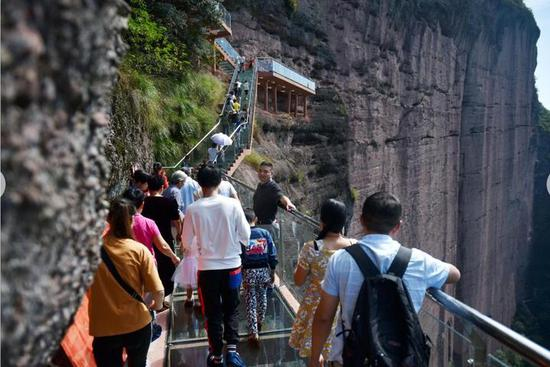 游人们享受着玻璃栈道带来的新奇与刺激的体验。