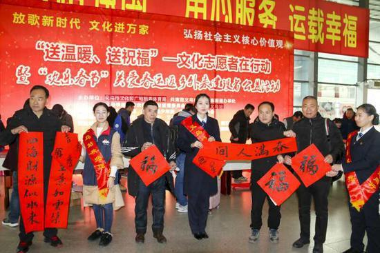 书法家为返乡旅客写春联送福字 。 义乌站提供