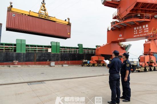 海关关员监管集装箱装上货轮退运