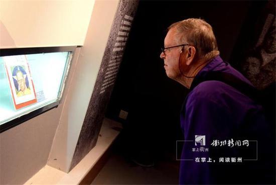 一位外国观众在观看馆藏文物——以杜立特为封面的《时代》杂志