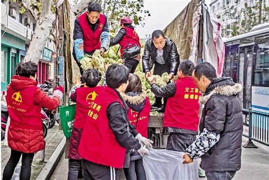 志愿者们帮忙搬运蔬菜。