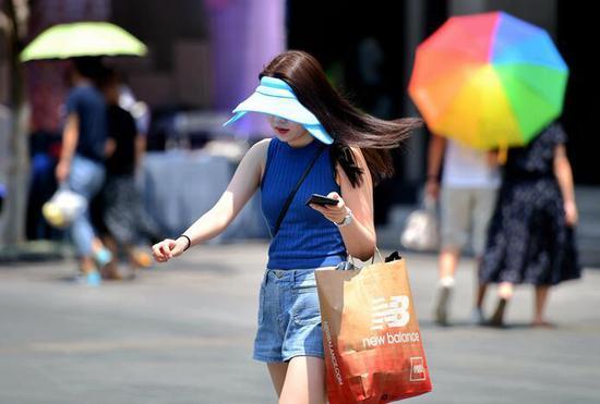 本周酷热难耐,市民用各种方法防晒。时补法摄