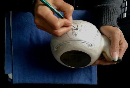 画师在毛样上用铅笔绘画,工匠再雕刻出精美的作品。 记者 包敦远 摄