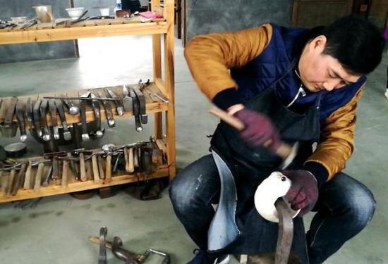 程志芳正在精心打磨银壶。 记者 包敦远 摄