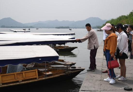 图为:游客正准备乘船游西湖。 王刚 摄