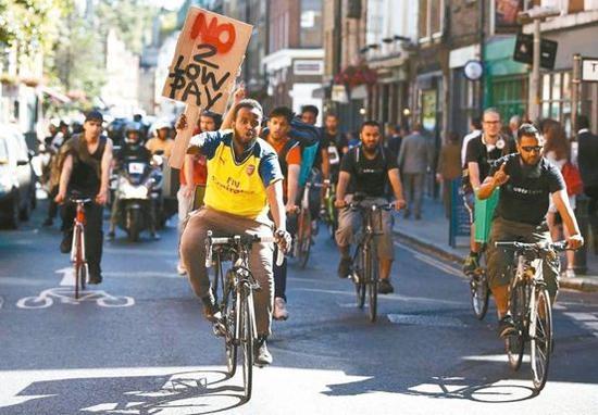 伦敦的餐饮外送员上街抗议薪资过低。