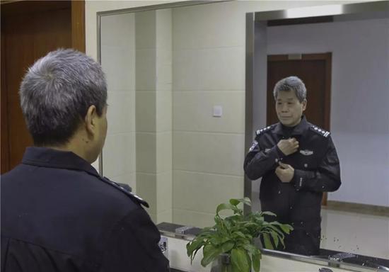 图为:方良明对着镜子仔细地整理警服 刘冰菲 摄