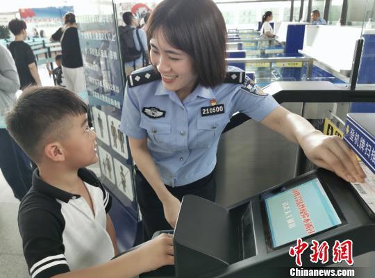 工作人员协助儿童使用自助通道。杭州出入境边防检查站 供图