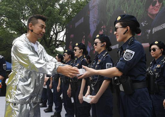 图为:赵文卓向西湖女子巡逻队赠送纪念物。王刚 摄